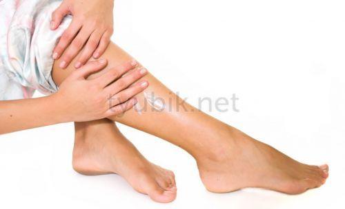 Девушка мажет ногу